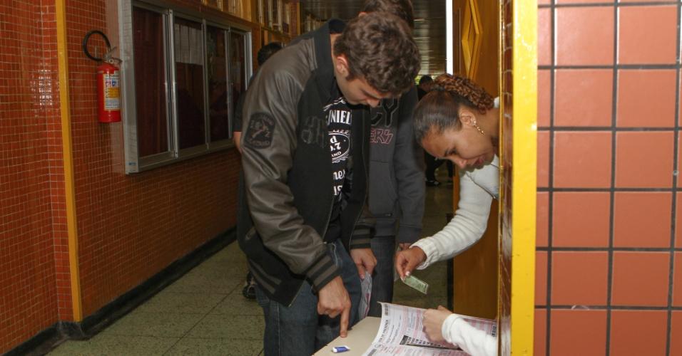 26.out.2013 - Fiscal confere dados de candidato no primeiro dia do Enem na PUC, em Curitiba