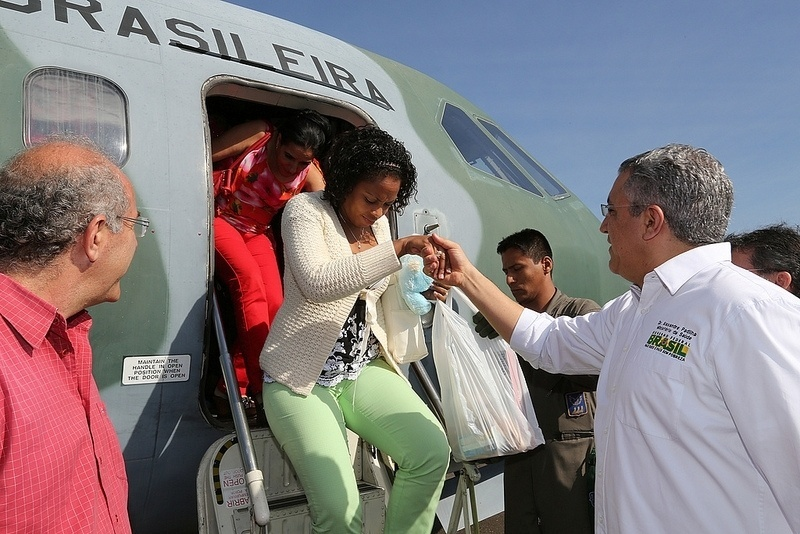 26.out.2013 - O ministro da Saúde, Alexandre Padilha, ajuda mulher a descer de avião da FAB durante a recepção de 57 profissionais estrangeiros que chegaram em Goiânia para trabalhar pelo programa Mais Médicos