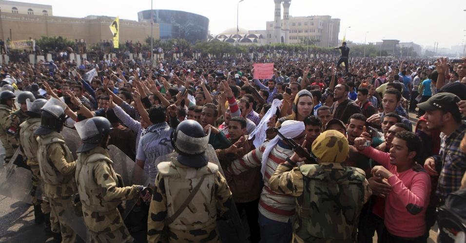 28.out.2013 - Estudantes da Universidade Al-Azhar, que são membros da Irmandade Muçulmana e simpatizantes do deposto presidente egípcio, Mohammed Mursi, protestam em frente ao ministério do Interior, enquanto soldados do Exército tentam impedi-los de marchar em direção à praça Rabaa no Cairo