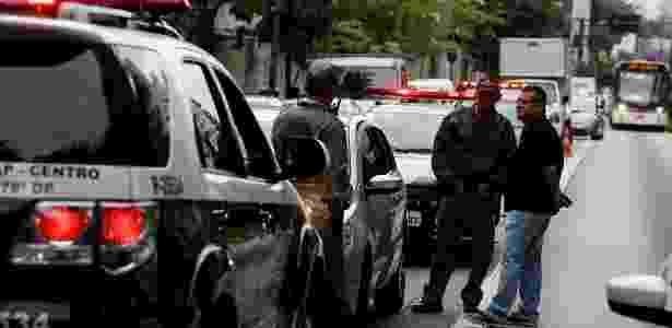 28.out.2013 - Policiais preservam o local onde um casal que estava em um carro com placa da cidade de Bauru, no interior de São Paulo, foi baleado. O crime aconteceu na esquina da alameda Lorena com avenida Nove de Julho, na região central de São Paulo, nesta segunda-feira (28) - Jorge Araujo/Folhapress