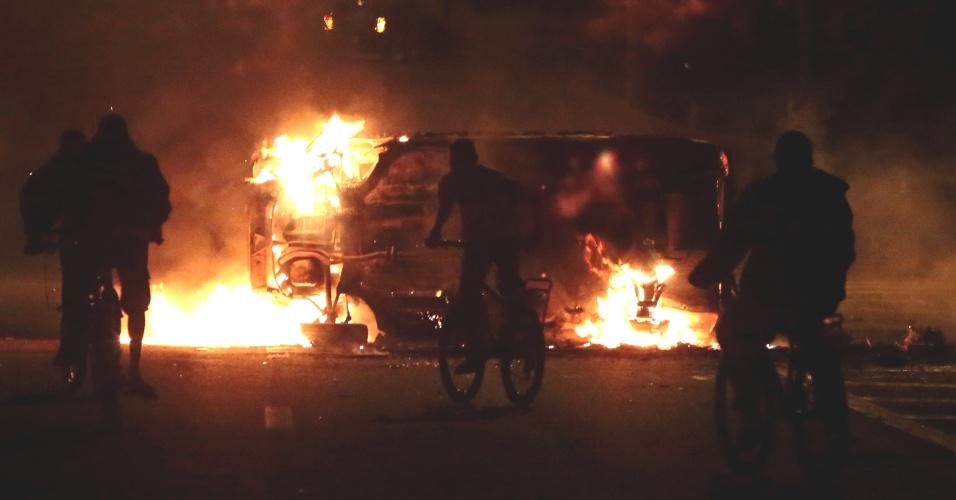 28.out.2013 - Ciclistas passam nesta segunda-feira (28) por carro incendiado durante protestos na região do Jaçanã, na zona norte de São Paulo. Cerca de 500 manifestantes, de acordo com a polícia, protestaram contra a morte de um adolescente durante uma abordagem de policiais militares ocorrida no domingo (27). Ao menos 90 pessoas foram detidas