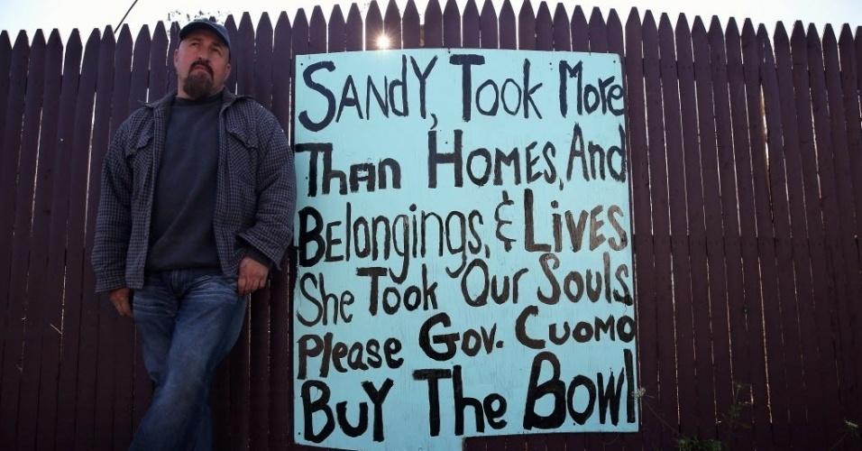 29.out.2013 - Joe Herrnkind se encosta na cerca de sua casa em Ocean Breeze, Nova York, onde ele afixou um cartaz no qual se lê: