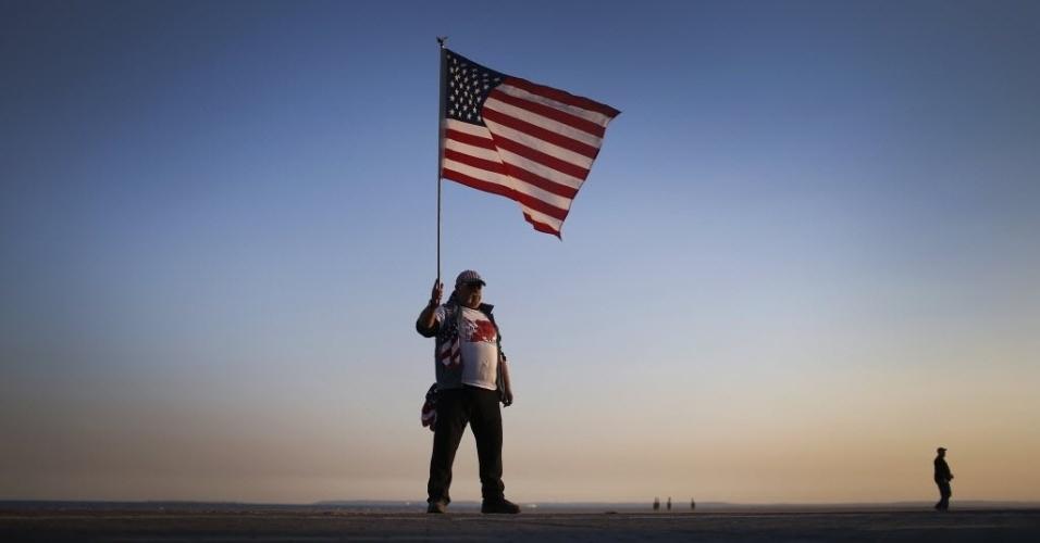 29.out.2013 - John Childs, que perdeu sua casa em Staten Island, Nova York, durante a passagem do furacão Sandy, segura bandeira dos EUA na praia durante evento em homenagem às vítimas nesta terça-feira (29). A passagem da supertempestade, que matou pelo menos 159 pessoas, danificou mais de 650 mil casas, e trouxe prejuízos estimados em US$ 70 bilhões para o país, completa um ano nesta terça-feira