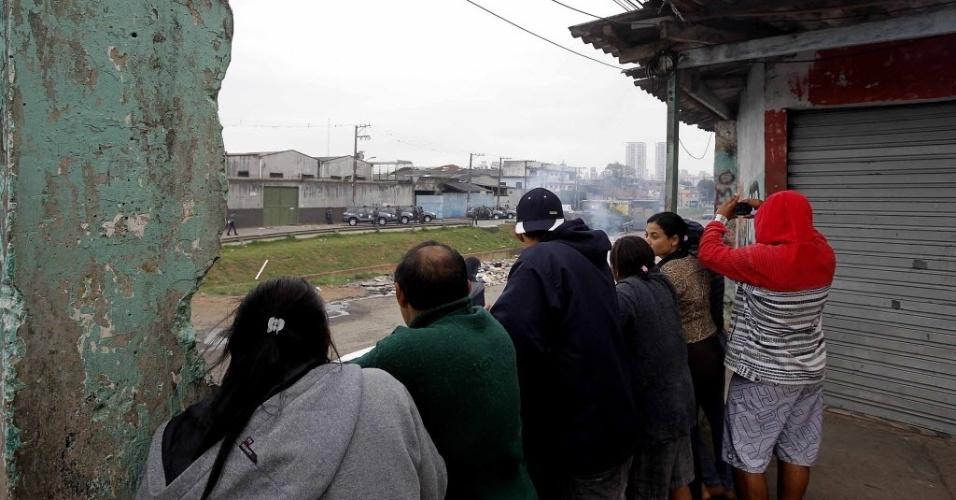 29.out.2013 - Moradores observam movimentação em rua na região do Parque Novo Mundo, na zona norte de São Paulo, nesta terça-feira (29), depois de protesto contra a morte de um adolescente durante uma abordagem policial ocorrida no domingo (27)
