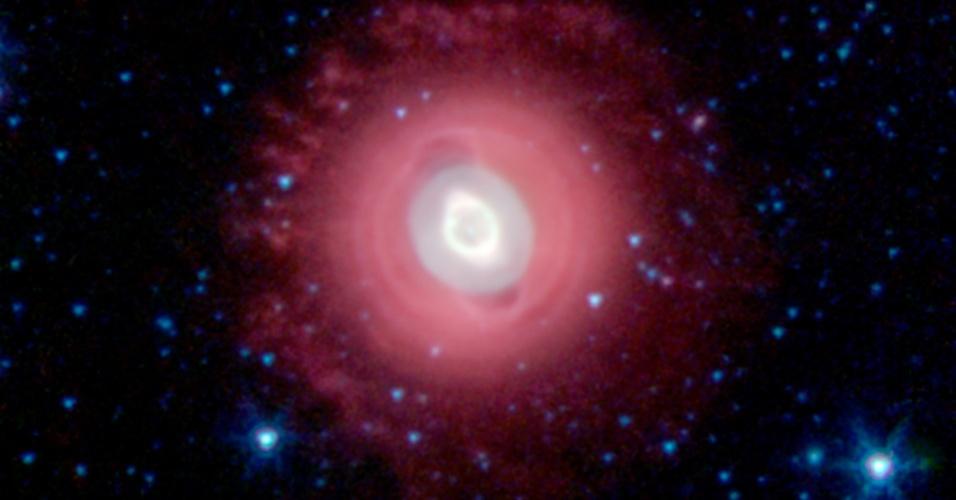 30.out.2013- A nebulosa Fantasma de Júpiter, também conhecida como NGC 3242, fica a cerca de 1.400 anos-luz de distância na constelação de Hidra. Nesta visão infravermelha do telescópio Spitzer da Nasa (Agência Espacial Norte-Americana), o halo exterior mais frio da estrela que está morrendo aparece em vermelho. Os anéis concêntricos ao redor do objeto, fruto de material que está sendo lançado periodicamente