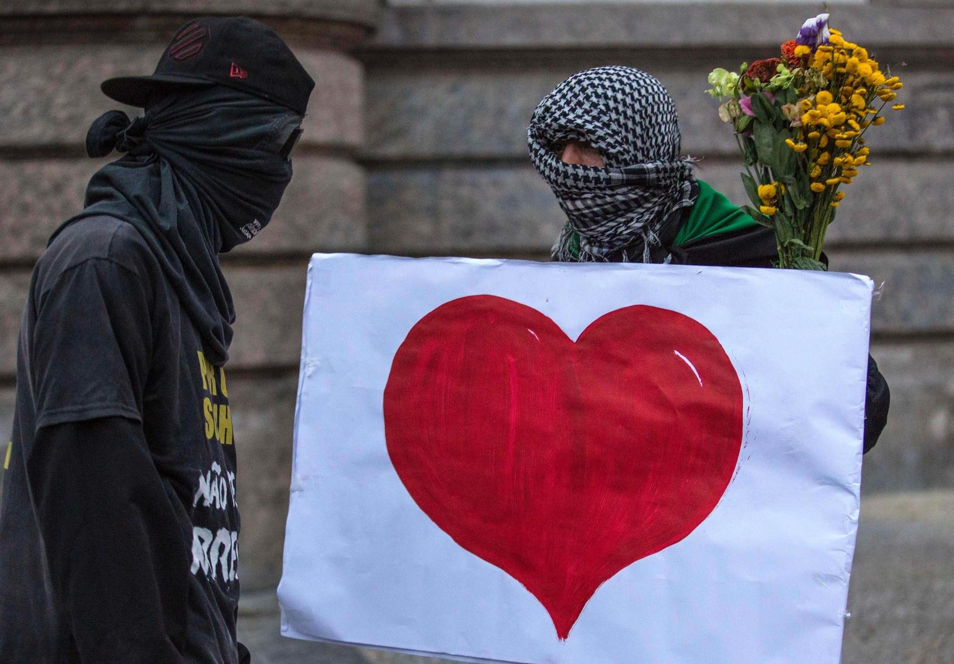 31.out.2013 - 31.out.2013 - Com rostos cobertos, segurando flores e um cartaz com um coração desenhado, manifestantes mascarados participam do ato