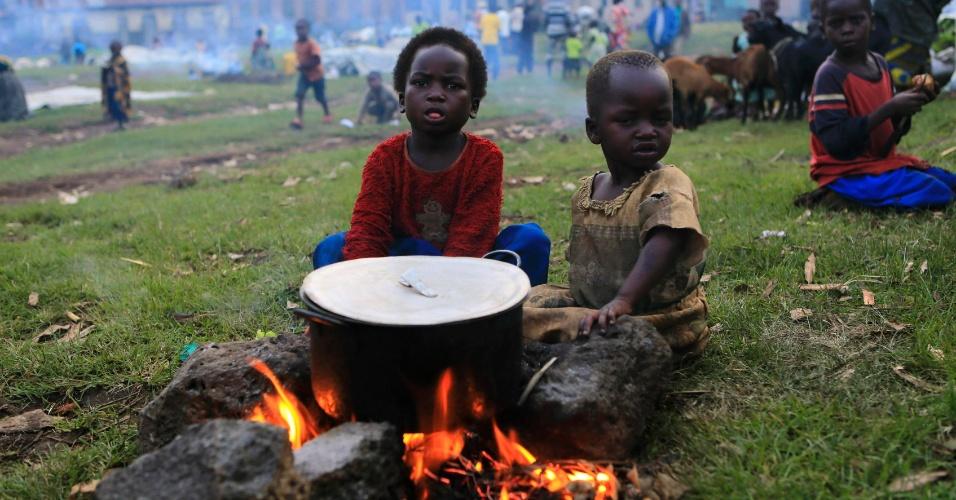 31.out.2013 - Crianças sentam ao redor de uma panela sobre um fogo em um campo de famílias desalojadas pela guerra civil entre o Exército congolês e rebeldes, em Bunagan, a 491 km a oeste da capital Kampala, nesta quinta-feira (31)