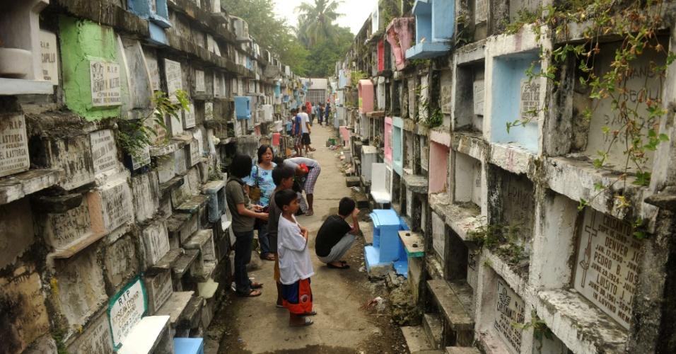 31.out.2013 - Filipinos visitam cemitério nesta quinta-feira (31) em Manila. O país celebra nesta semana uma tradição anual cristã em respeito aos mortos, incluindo o Dia de Todos os Santos (1º de novembro) e o Dia de Todas as Almas (2 de novembro)