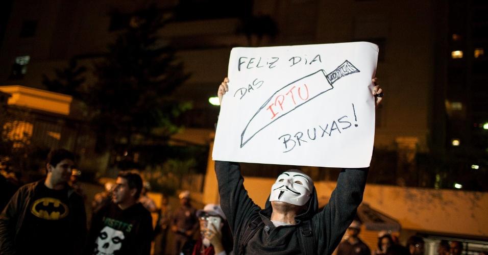 31.out.2013 - Manifestante mascarado segura cartaz durante protesto contra o reajuste do IPTU (Imposto Predial e Territorial Urbano), na noite desta quinta-feira (31) na avenida Paulista, na área central de São Paulo. De acordo com a Polícia Militar, cerca de 150 pessoas participaram do ato. Segundo a CET (Companhia de Engenharia de Tráfego), eles bloquearam a avenida Paulista, no sentido Consolação, até as 22h30