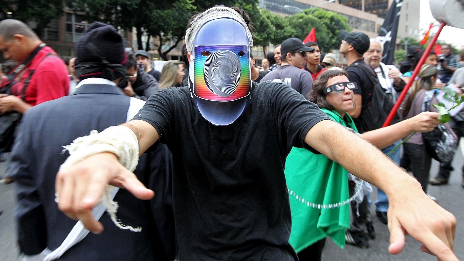 31.out.2013 - Manifestante usa máscara da rede Globo de televisão durante o ato