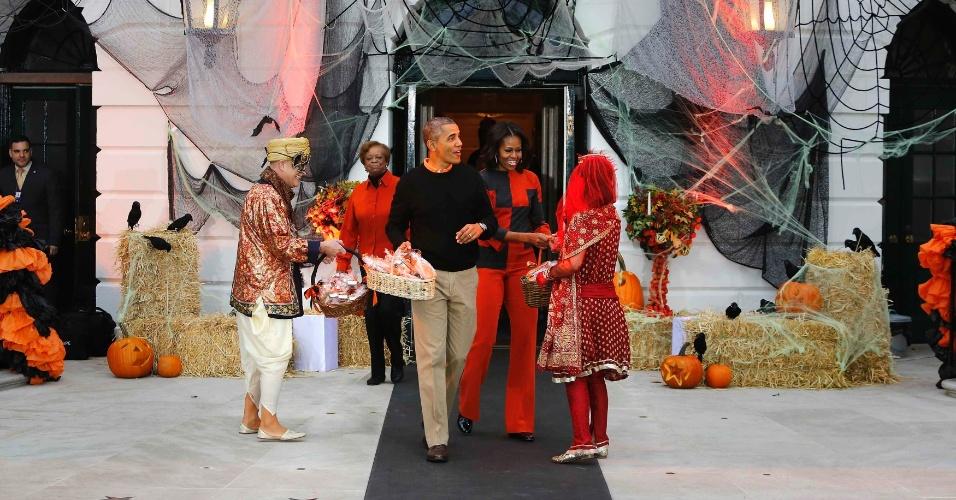 31.out.2013 - O presidente dos Estados Unidos, Barack Obama, e a primeira-dama, Michelle Obama, carregam cestas com doces para entregar a crianças na Casa Branca, em Washington, nesta quinta-feira (31)