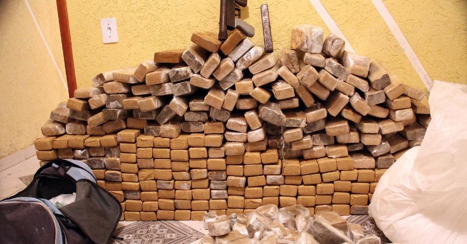 31.out.2013 - Policiais da Rota (tropa de elite da PM) apreenderam mais de 500 kg de drogas, armas, dinheiro e materiais para o preparo de drogas em uma casa no Jaçanã, zona norte de São Paulo, nesta quarta-feira (30). Segundo a Polícia Militar, eles chegaram até o local após denuncias. Dois suspeitos que guardavam o local, que tinha uma central de monitoramento, foram presos. Todo o material apreendido foi levado para o Denarc (departamento de narcóticos)