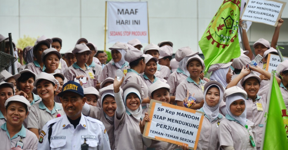 """31.out.2013 - Trabalhadores de fábrica exibem cartaz com o texto """"Desculpe, nós paramos a produção hoje? nesta quinta-feira (31), em Jacarta (Indonésia). Trabalhadores em toda o país começam nesta quinta uma greve de dois dias, reivindicando aumento salarial"""