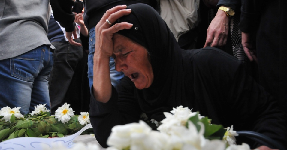 31.out.2013 - Uma familiar de um dos 34 imigrantes libaneses que morreram afogados em águas da Indonésia chora sobre um caixão em funeral na cidade de Trípoli, na Líbia, nesta quinta-feira (31)