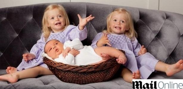 O bebê Joel Brandon Jr., apelidado de JJ, entre suas irmãs gêmeas