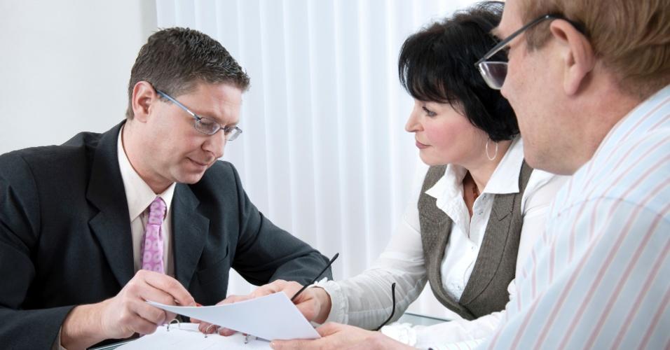 Casal negocia com vendedor; negociação, dívida, casal, assinatura, contrato