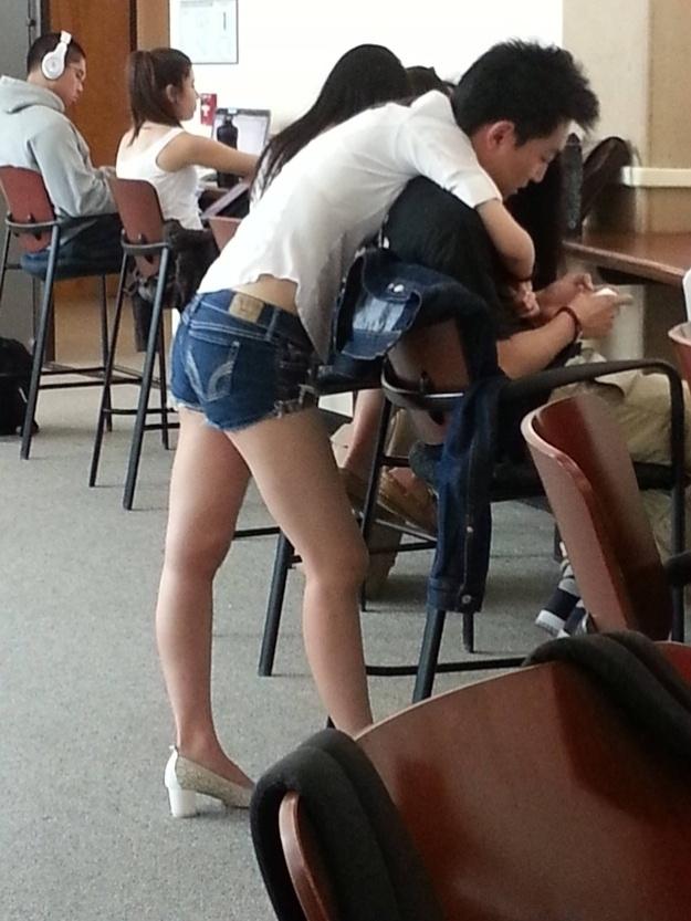 5.nov.2013 - Esse jovem não tem pernas de mulher. Eles está sendo abraçado por uma enquanto mexe no seu celular