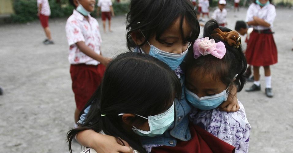 6.nov.2013 - Alunos usam máscaras cirúrgicas para se protegerem de cinzas vulcânicas, em escola em Tiga Ndreket aldeia no distrito de Karo, Indonésia. O vulcão Monte Sinabung continuou a expelir cinzas nesta quarta-feira (6). As crianças estão frequentado escolas em áreas que não pertencem aos locais evacuados