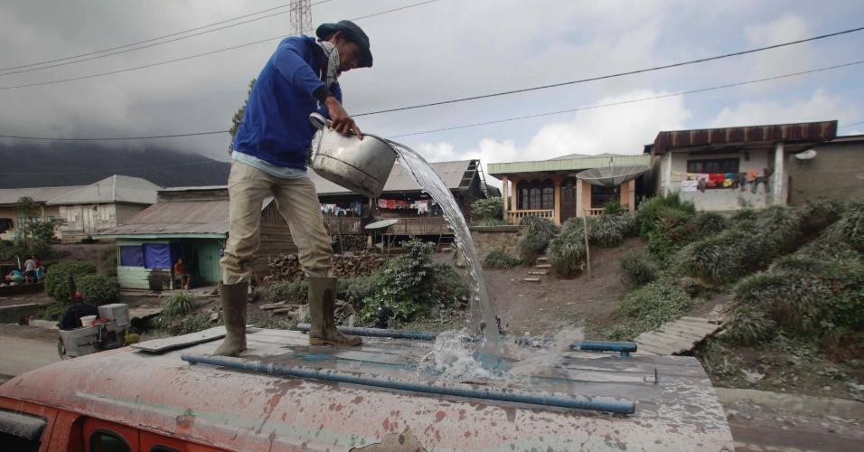 7.nov.2013 - Homem lava veículo coberto por cinzas vulcânicas na vila de Kutagugung, na Indonésia. O vulcão Monte Sinabung continua expelindo cinzas nesta quinta-feira (7), enquanto milhares de residentes das áreas próximas permanecem em abrigos temporários, com medo de novas erupções