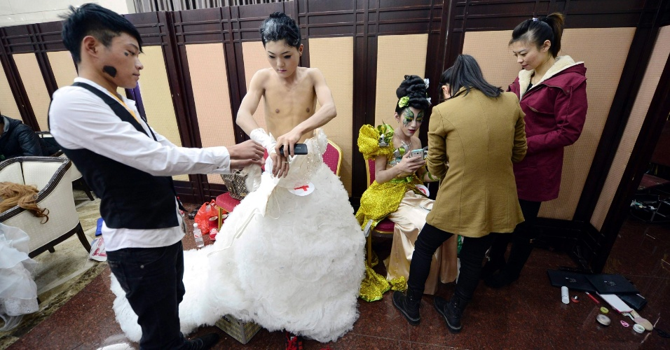7.nov.2013 - Modelo coloca vestido de noiva durante competição de maquiagem em Jinan, na província de Shandong (China), nesta quarta-feira (6). Cada participante do concurso de maquiagem recebe um modelo do sexo masculino e tem que deixá-lo com a aparência mais feminina possível