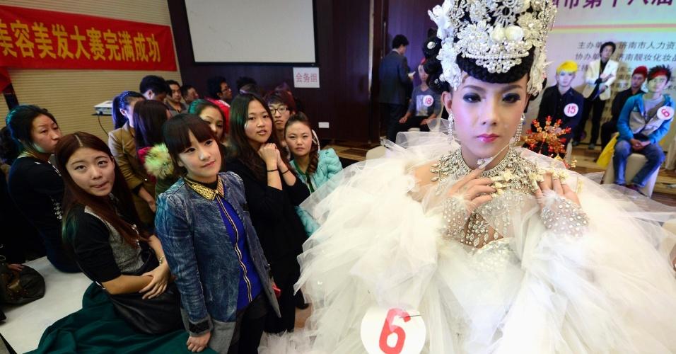 7.nov.2013 - Público observa participante de concurso de maquiagem em Jinan, na província de Shandong (China), nesta quarta-feira (6). Cada participante do concurso de maquiagem recebe um modelo do sexo masculino e tem que deixá-lo com a aparência mais feminina possível