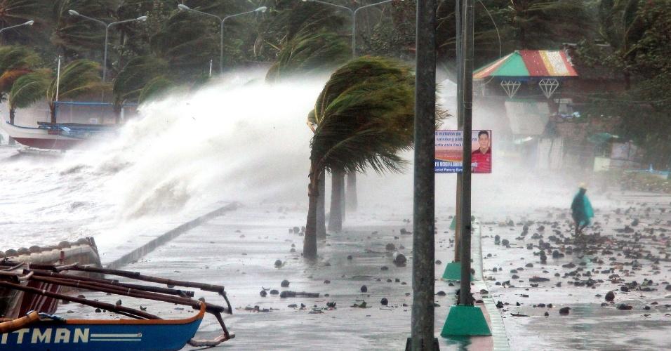 8.nov.2013 - Morador caminha ao lado de fortes ondas que se chocam contra o quebra-mar na cidade filipina de Legazpi, no centro do país, causadas pelo tufão Haiyan, nesta sexta-feira (8). A tempestade, chamada de Yolanda nas Filipinas, é uma das mais intensas jamais registradas e causou, até esta manhã, a morte de três pessoas. Milhares ficaram assustados com os ventos de até 315 km/h que arrancaram telhados de edifícios e ondas gigantes que arrastaram casas à beira-mar