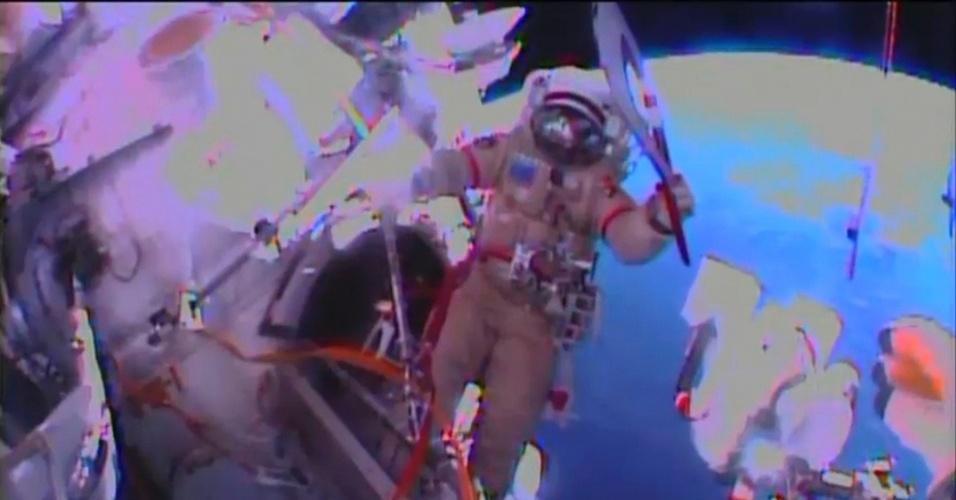 9.nov.2013 - Astronauta da Estação Espacial Internacional caminha fora da nave com a tocha das Olimpíadas de Inverno, neste sábado (9). Dois cosmonautas russos levaram a tocha apagada para sua primeira caminhada espacial. Os Jogos começam na Rússia, no ano que vem