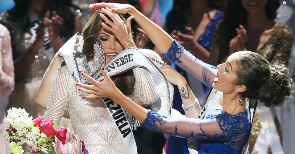 9.nov.2013 - Eleita Miss Universo 2013, a Miss Venezuela Gabriela Isler tenta, em vão, segurar a coroa que foi entregue pela vencedora da edição de 2012, a norte-americana Olivia Culpo, durante a cerimônia em Moscou, na Rússia. A nova miss não perdeu o rebolado e recolocou a coroa na cabeça logo em seguida