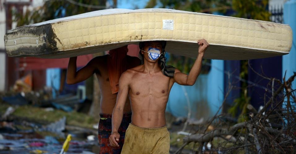 10.nov.2013 - Dois homens carregam colchão encharcado em bairro mais atingido de Tacloban, nas Filipinas, em meio a destruição causada pela passagem do tufão Haiyan, considerado o mais poderoso já registrado na história, com ventos de até 315 km/h