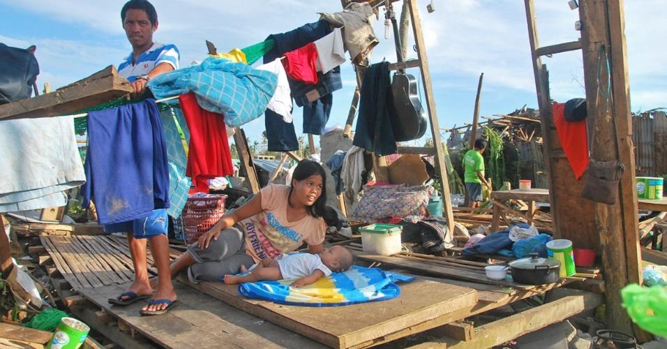 10.nov.2013 - Família fica sobre os escombros da casa onde moravam e que foi destruída com a passagem do tufão Haiyan  na província de Cebu, nas Filipinas