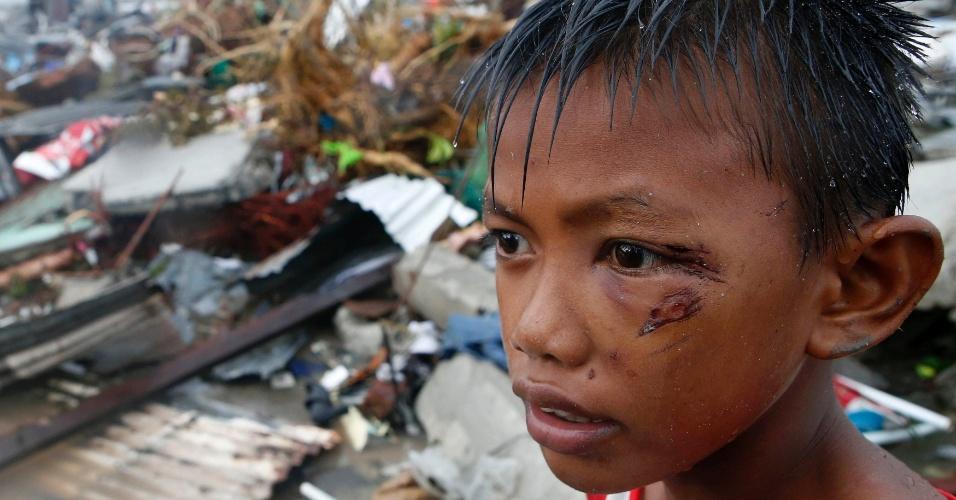 10.nov.2013 - Menino ferido durante passagem do tufão Hayan procura por pertences nos destroços de sua casa, em Tacloban (Filipinas). O tufão Haiyan, uma das tempestades mais fortes já registradas, matou ao menos 10 mil pessoas na província, segundo a polícia