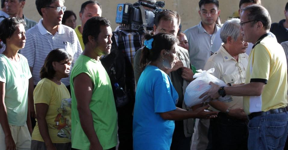 10.nov.2013 - O presidente filipino, Benigno Aquino (dir.), distribui kits humanitários às vítimas do tufão Haiyan, na cidade de Leyte