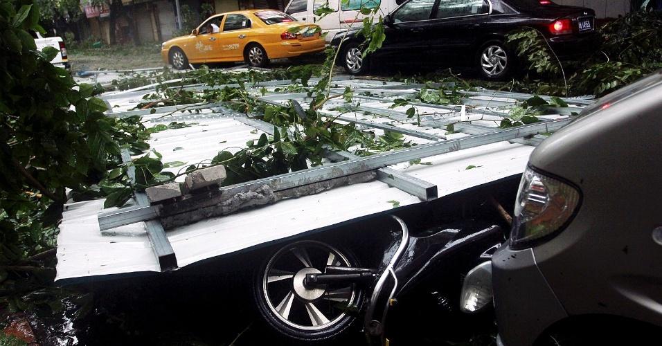 10.nov.2013 -  Outdoor cai em cima de motocicleta devido aos ventos fortes causados pelo tufão Haiyan, que se aproxima da cidade de Sanya, no sul da província chinesa de Hainan. As autoridades da China ativaram neste domingo o alerta vermelho, o de maior gravidade, perante a chegada do tufão; cerca de 200 voos foram cancelados nos aeroportos de Sanya e Haikou