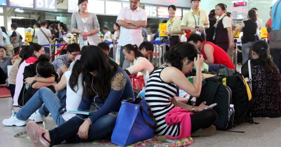 10.nov.2013 - Passageiros que tiveram voos cancelados se aglomera no aeroporto de Sanya, no sul da província chinesa de Hainan. As autoridades da China ativaram neste domingo o alerta vermelho, o de maior gravidade; cerca de 200 voos foram cancelados nos aeroportos de Sanya e Haikou