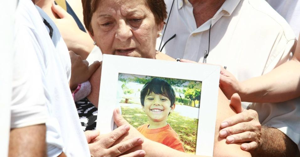 11.nov.2013 - A avó do menino Joaquim Ponte Marques, 3, Maria Cristina Mingoni Ponte, segura foto do garoto  durante enterro do garoto no cemitério municipal de São Joaquim da Barra (SP), nesta segunda-feira (11)