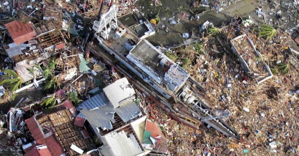 11.nov.2013 - Em imagem divulgada pela Força Aérea filipina de região devastada pelo tufão Haiyan em Tacloban, uma embarcação aparece entre os escombros de edifícios. Ondas causadas pelo tufão levaram barcos a região com casas. Autoridades estimam que ao menos 10 mil filipinos morreram no desastre natural