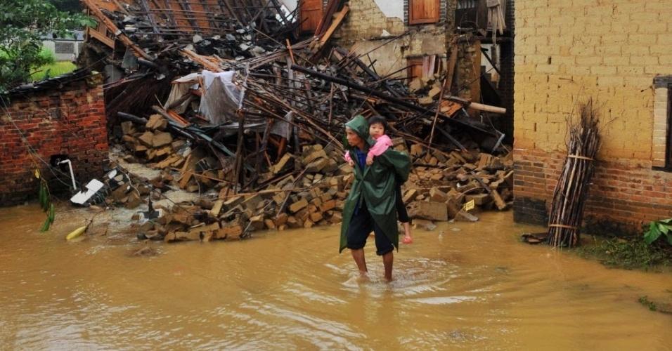 11.nov.2013 - Mulher carrega criança em rua inundada na cidade de Yong'an, na China. o tufão Haiyan trouxe fortes ventos e chuvas ao país depois de ter devastado cidades filipinas. O tufão perdeu força ao tocar a terra no Vietnã