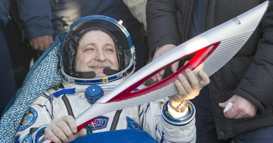 11.nov.2013 - O cosmonauta russo Fyodor Yurchikhin segura a tocha dos Jogos Olímpicos de Inverno de 2014 após desembarcar da Soyuz, perto da cidade de Zhezkazgan (Cazaquistão)