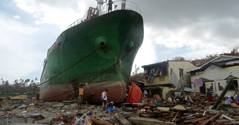 11.nov.2013 - Pessoas andam sobre os escombros próximo ao um navio levado para a terra pelas fortes ondas formadas pelo tufão Haiyan em Tacloban