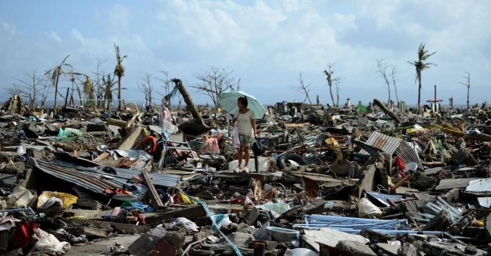 11.nov.2013 - Sobrevivente caminha em meio aos escombros de casas destruídas pelo tufão Haiyan em Tacloban, nesta segunda-feira (11). Três dias depois do supertufão ter destruído cidades inteiras na região central das Filipinas, deixando áreas repletas de cadáveres, os sobreviventes estão sem comida, água e medicamentos
