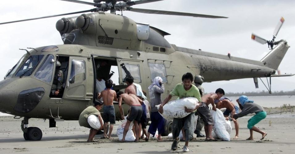 11.nov.2013 - Sobreviventes do tufão Haiyan na vila de Capiz carregam sacos com mantimentos básicos trazidos por helicóptero das Forças Armadas filipinas nesta segunda-feira (11). Autoridades estimam que ao menos 10 mil filipinos morreram no desastre natural