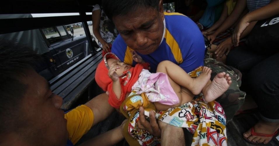 12.nov.2013 - Bebê que sobreviveu a passagem do tufão Haiyan é retirada da área do desastre em um caminhão militar junto com a família. A ONU pediu nesta terça-feira (12) US$ 301 milhões em ajuda humanitária para os filipinos afetados pelo tufão Haiyan, que teria matado ao menos 10.000 pessoas
