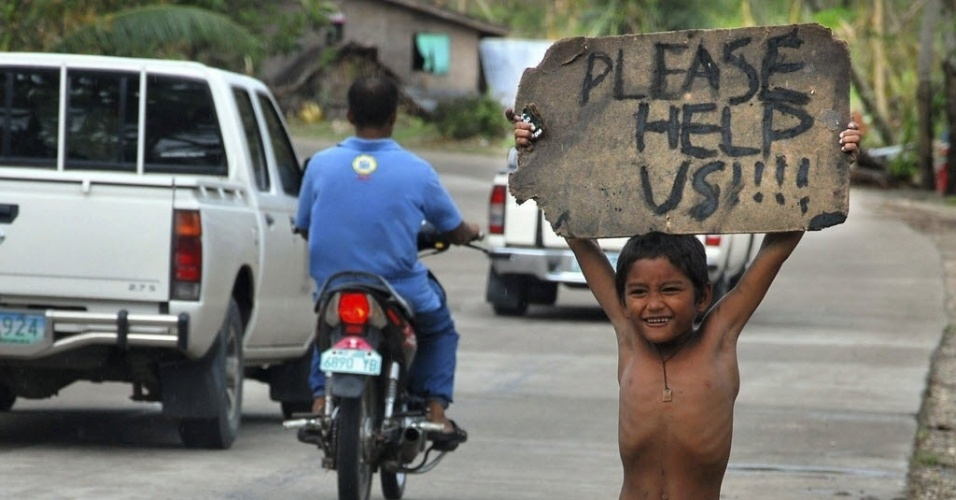 """12.nov.2013 - Criança pede ajuda para carros que passam por estrada de Cebu nas Filipinas. Pelo menos 1.744 pessoas morreram nas Filipinas durante a passagem do tufão """"Haiyan"""", informaram nesta terça-feira (12) os órgãos oficiais do país"""