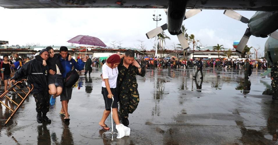 12.nov.2013 - Feridos são resgatados e embarcam em avião militar no aeroporto de Tacloban, região central das Filipinas, após a passagem do tufão Haiyan. Na cidade, uma das mais atingidas no maior desastre natural do país, ao menos 10.000 pessoas morreram, o correspondente a 5% da sua população; com problemas no abastecimento, lojas foram invadidas e saqueadas