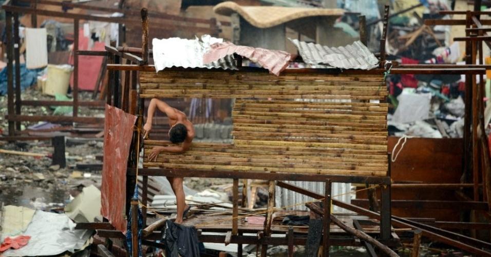 12.nov.2013 - Homem reconstrói casa destruída em Tacloban, leste da ilha de Leyte nas Filipinas. Milhares de sobreviventes do tufão Haiyan nas Filipinas, que teria provocado mais de 10.000 mortes, aguardavam nesta terça-feira água e comida com urgência, no mesmo dia em que seguiram para a região da catástrofe barcos de ajuda americanos e britânicos