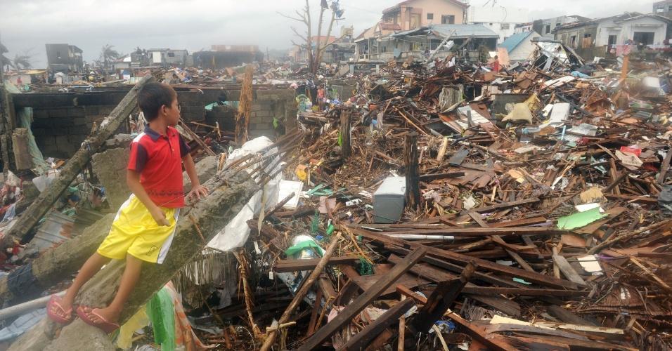12.nov.2013 - Menino observa escombros de casas destruídas pela passagem do tufão Haiyan na cidade de Tacloban, na região central das Filipinas