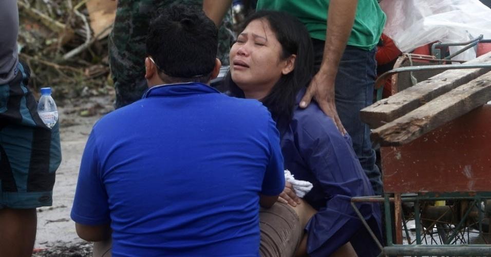 12.nov.2013 - Mulher chora depois de encontrar o corpo de um parente que estava desaparecido, junto a outras vítimas do tufão Haiyan, na cidade de Tacloban, Filipinas