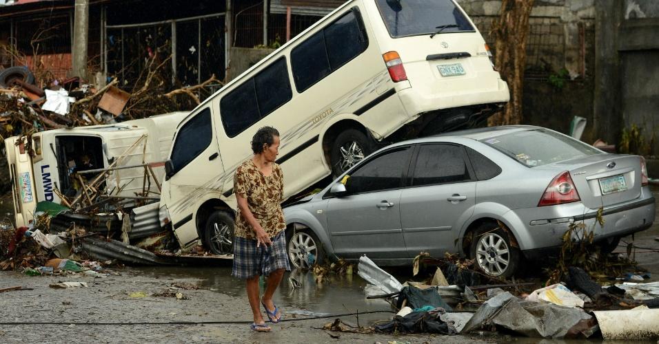 12.nov.2013 - Mulher passa por carros que ficaram empilhados após a passagem do tufão Haiyan pela cidade de Tacloban, no centro das Filipinas.