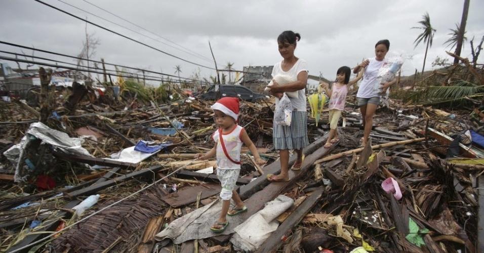 12.nov.2013 - Sobreviventes da passagem do tufão Haiyan pelas Filipinas andam sobre escombros nesta terça-feira (12)