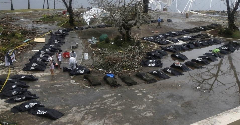 12.nov.2013 - Sobreviventes observam sacos com corpos de vítimas do tufão Haiyan na cidade de Tacloban, nas Filipinas, nesta terça-feira (12). Equipes de resgate tentaram chegar em locais isolados. Segundo autoridades, o número de mortos, que passa de 10 mil, pode aumentar rapidamente com a intensificação dos esforços nas buscas por vítimas